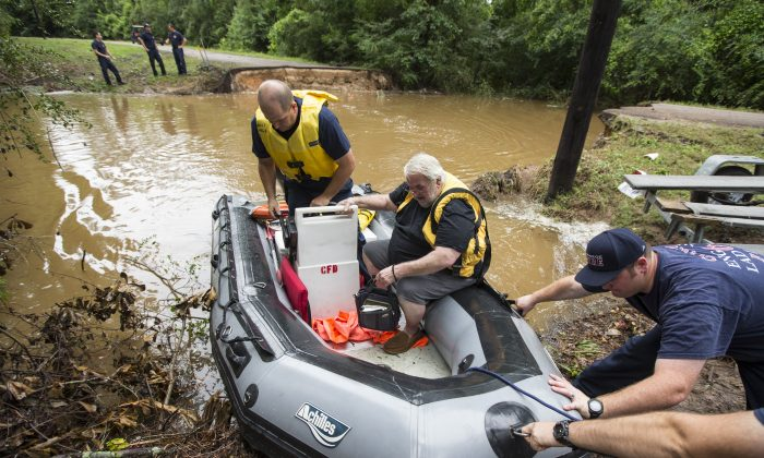 Conroe firefighters evacuate Jim Treadway via boat after Treadway was stranded when Pecan Bend Road was washed out near the San Jacinto River in Conroe, Texas, on May 27, 2016. (Brett Coomer/Houston Chronicle via AP)
