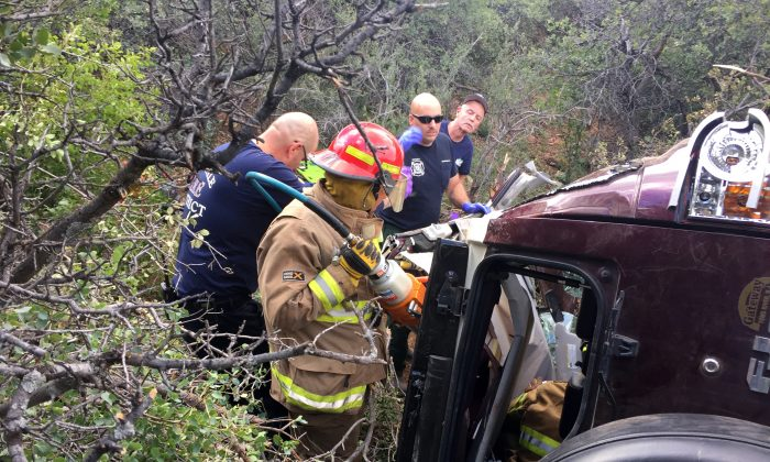 This photo provided by Kim Moore shows firefighters working to extricate a 50-year-old man from his crashed car on Mingus Mountain in Yavapai County, Arizona on Friday, May 27, 2016. (Kim Moore via AP)