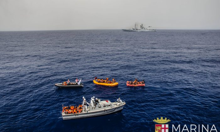 Rescuers tow migrants to board the Italian Navy ship Vega, after the boat they were aboard sunk in the Mediterranean Sea, off the Libyan coast, on May 27, 2016. (Raffaele Martino/Marina Militare via AP Photo)