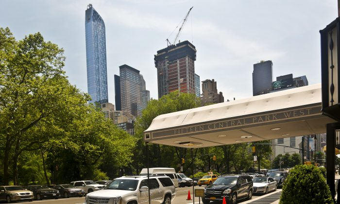 """A luxury 90-floor apartment skyscraper called """"One57,"""" left, rises above all other buildings overlooking Central Park, while a crane sits atop ongoing construction for a new condominium skyscraper at 220 Central Park South, Thursday May 26, 2016, in New York. A penthouse in One57 went for $100.5 million in 2014, but an apartment in the new condominium is expected to sell for $250 million. (AP Photo/Bebeto Matthews)"""