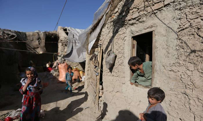 In this Monday, May 30, 2016 photo, Afghan children play at their temporary home in a camp for internally displaced people in Kabul, Afghanistan. Amnesty International said Tuesday, May 31,  that more than 1.2 million Afghans have been forced to flee their homes due to violence in the past three years and urged the Kabul government and the international community to tackle the country's growing crisis of refugees internally displaced by war. (AP Photo/Rahmat Gul)