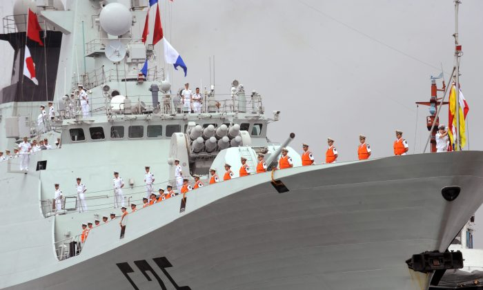 People's Liberation Army (PLA) Navy sailors stand on the deck of a Chinese warship at the international port in Manila on April 13, 2010. (Ted Aljibe/AFP/Getty Images)
