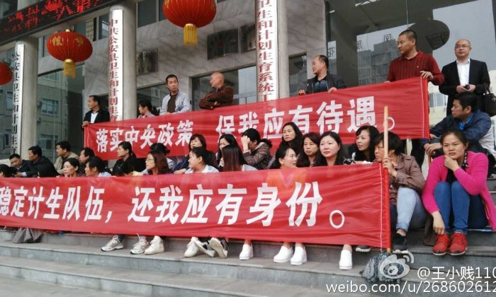 Family planning officials of Gongan County hold banners to protest their income woes. (Sina Weibo)