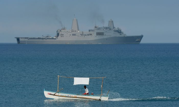 A Filipino fisherman is seen past the U.S. Navy amphibious transport dock ship USS Green Bay (LPD-20) during an amphibious landing exercise on a beach at San Antonio, Zambales Province, on April 21, 2015, as part of annual Philippine-U.S. joint maneuvers some 137 miles (220km) east of the Scarborough Shoal in the South China Sea. (Ted Aljibe/AFP/Getty Images)