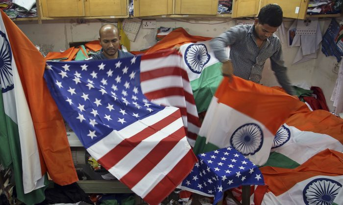 An Indian men fold the U.S. and Indian flags at a shop in Mumbai, India, on Jan. 24, 2015, in this file photo. (Rajanish Kakade/AP Photo)