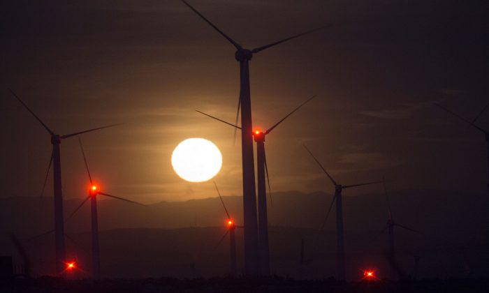 The moon rises behind electric energy generating wind turbines seen on a wind farm in the San Gorgonio Pass area, near Palm Springs, Calif., on Earth Day, on April 22, 2016. (David McNew/AFP/Getty Images)