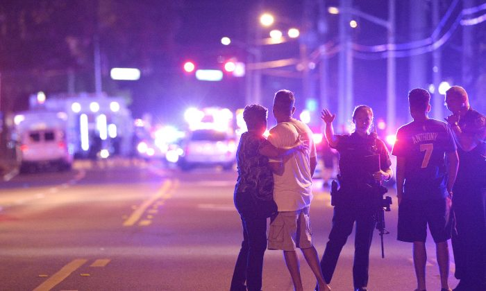 Orlando Police officers direct family members away from a fatal shooting at Pulse Orlando nightclub in Orlando, Fla., on June 12, 2016. (AP Photo/Phelan M. Ebenhack)
