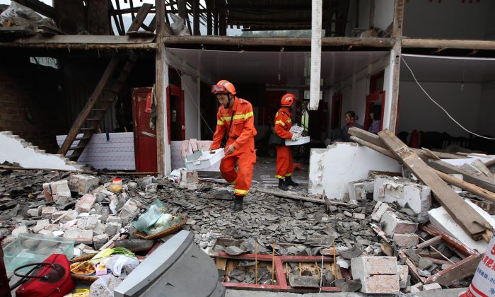 Rescuers help recover valuables from a damaged home after an earthquake hit Lushan County in Ya'an City, southwest China's Sichuan Province, on April 21, 2013. (STR/AFP/Getty Images)