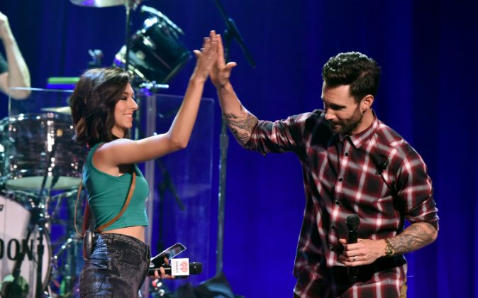 Singers Christina Grimmie (L) and Adam Levine speak onstage during the iHeartRadio Album Release Party with Maroon 5 LIVE on the CW at iHeartRadio Theater in Burbank, Calif., on Aug. 26, 2014. (Kevin Winter/Getty Images for Clear Channel)