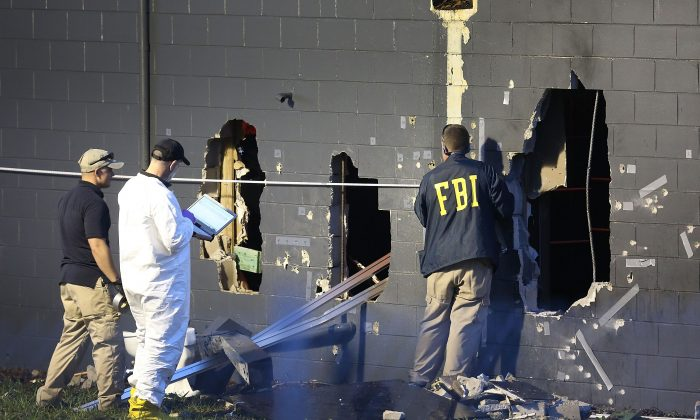 Police officials investigate the back of the Pulse nightclub after a shooting involving multiple fatalities at the nightclub in Orlando, Fla., Sunday, June 12, 2016. (AP Photo/Phelan M. Ebenhack)
