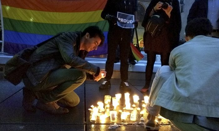 A man lights a candle during a spontaneous  vigil to remember those slain and wounded at an Orlando nightclub, Sunday June 12, 2016 in Paris. (AP Photo/Raphael Satter)