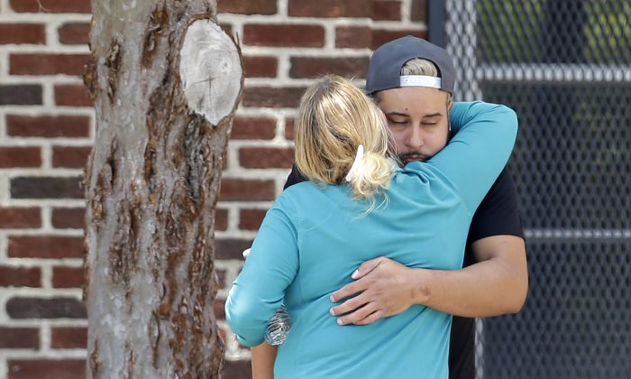 Family members of victims of the Orlando nightclub shooting hug outside a family reunification center set up at the Beardall Senior Center, Monday, June 13, 2016, in Orlando, Fla. (AP Photo/Alan Diaz)