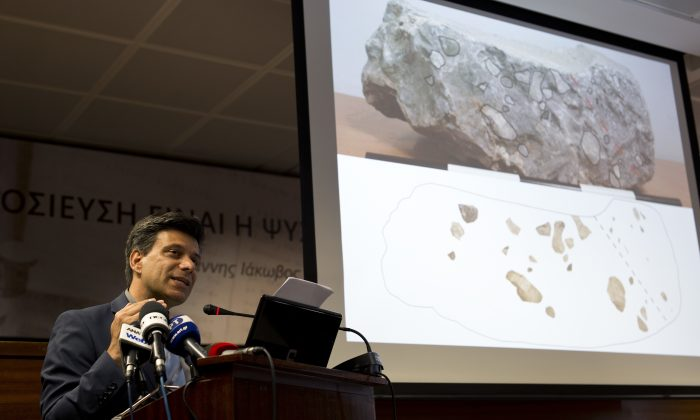 Greek archaeologist Christofilis Maggidis speaks as a photograph of a stone he believes belonged to the lost royal throne in the ancient palace of Mycenae, heart of the Mycenaean civilization, in southern Greece, during a press conference in Athens, on June 14, 2016. Maggidis says the worked stone, found by chance two years ago under the prehistoric citadel, is a chunk of the monolithic throne that was smashed when an earthquake sent part of the palace tumbling into a streambed below. (AP Photo/Petros Giannakouris)
