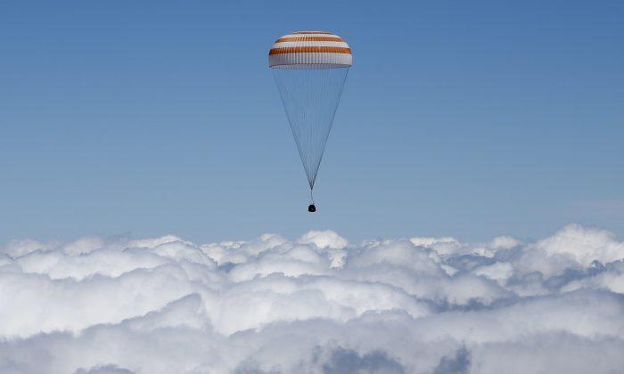 The Soyuz TMA-19M capsule carrying NASA's Tim Kopra, European Space Agency's Tim Peake, and Roscosmos' Yuri Malenchenko descends beneath a parachute near the town of Dzhezkazgan, Kazakhstan, on June 18, 2016. (Shamil Zhumatov/AP)