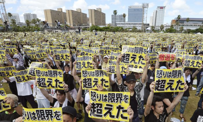 """Protesters hold placards that read: """"Our anger has reached its limit"""" during a protest rally against the presence of U.S. military bases on the southwestern island of Okinawa in Naha, Okinawa, on June 19, 2016 as many of them wearing black to mourn the rape and killing of a local woman in which a former U.S. Marine is a suspect. The rally called for a review of the U.S.-Japanese security agreement, which burdens Okinawa with hosting the bulk of American troops in Japan. (Ryosuke Uematsu/Kyodo News via AP)"""