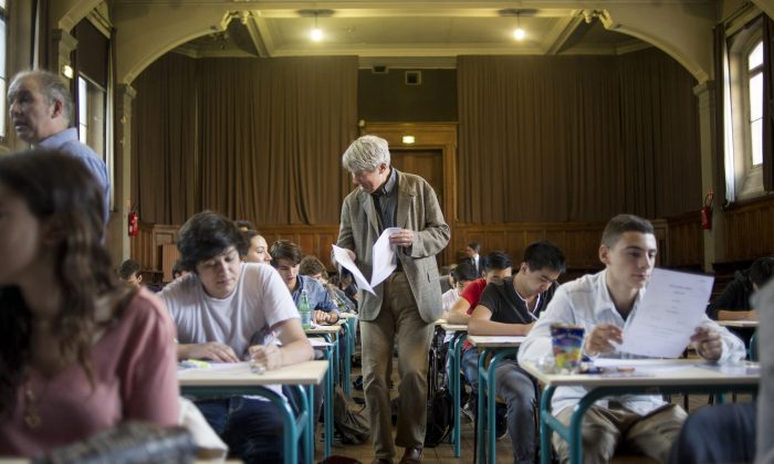 A teacher distributes final exams. (Fred Dufour/AFP/Getty Images)