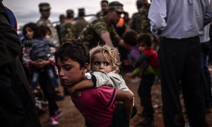 Syrian Kurdish people arrive at the border between Syria and Turkey after several mortars hit both side in the southeastern town of Suruc, Sanliurfa Province, on Sept. 29, 2014. (Bulent Kilic/AFP/Getty Images)
