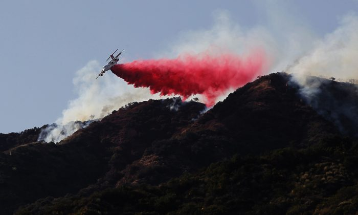 A firefighting plane in a file photo making a retardant drop on a hill near a wildfire in Azusa, Calif., in June 2016. (Nick Ut/AP Photo)