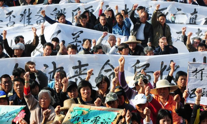Villagers hold banners and placards during a protest rally by residents of Wukan, a fishing village in the southern province of Guangdong, as they demand the government take action over illegal land grabs and the death in custody of a local leader on Dec. 19, 2011. (STR/AFP/Getty Images)