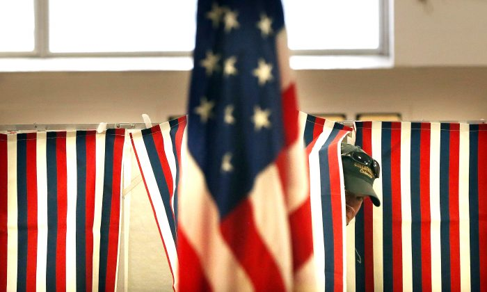 A man exits a voting booth inside a middle school serving as a voting station on the day of the New Hampshire Primary in Bow, N.H., on Feb. 9, 2016. (Spencer Platt/Getty Images)