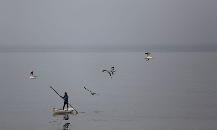 A Palestinian fisherman rides a boat on a foggy day in the Mediterranean Sea off the coast of Gaza City on April 5, 2016. (MOHAMMED ABED/AFP/Getty Images)