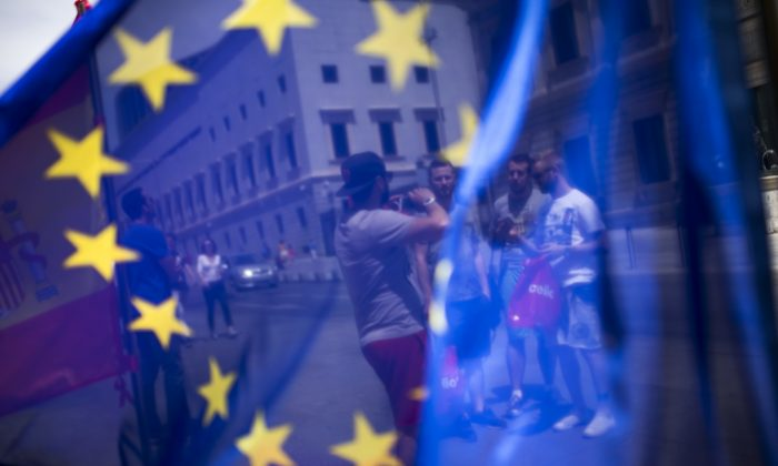 A group of tourists posing for a photograph in front of the Spanish Parliament is seen through the EU flag in Madrid, Spain, on June 24, 2016. (AP Photo/Francisco Seco)