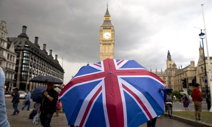 A pedestrian shelters from the rain beneath a Union flag themed umbrella as they walk near the Big Ben clock face and the Elizabeth Tower at the Houses of Parliament in central London on June 25, 2016. (Justin Tallis/AFP/Getty Images)