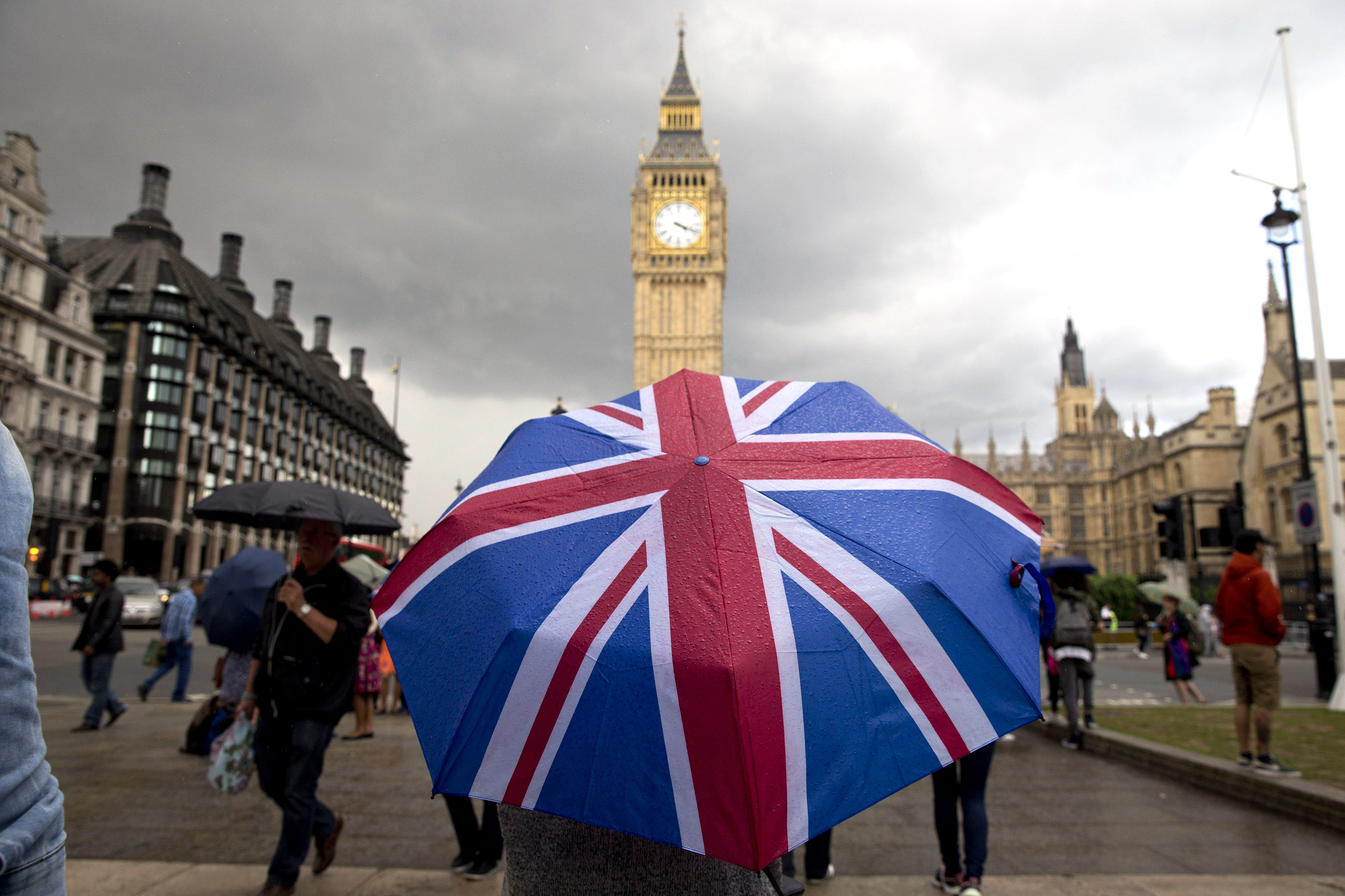 A pedestrian shelters from the rain beneath a Union flag themed umbrella as they walk near the Big Ben clock face and the Elizabeth Tower at the Houses of Parliament in central London on June 25, 2016, following the pro-Brexit result of the U.K.'s EU referendum vote. (Justin Tallis/AFP/Getty Images)