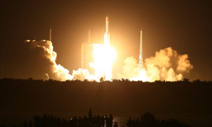 Spectators watch as a Long March 7 (CZ-7) rocket lifts off the launch pad in Wenchang in southern China's Hainan Province on June 25, 2016. (Chinatopix via AP)