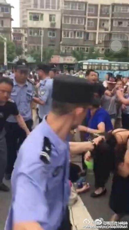 A policeman grabs a woman's hair. (via Sina Weibo)