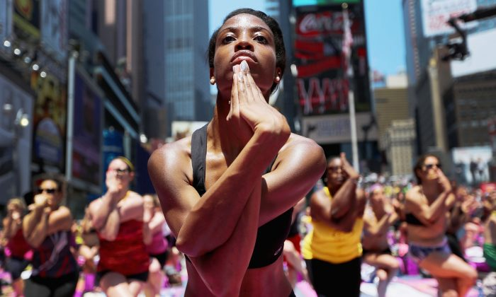 Aisha Johnson (C) and other enthusiasts perform yoga in Times Square during an event marking the summer solstice in New York City on June 21, 2013. (Mario Tama/Getty Images)