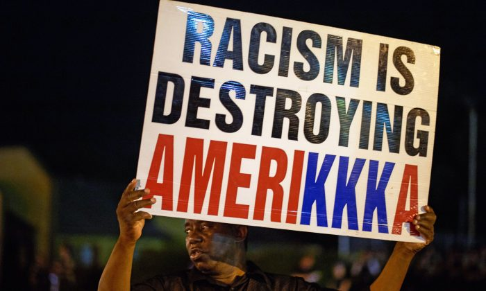 A man holds a sign during a protest on West Florissant Avenue in Ferguson, Missouri, on Aug. 10, 2015. (Michael B. Thomas/AFP/Getty Images)