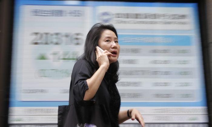 A woman walks passes a display of the Hang Seng Index at a bank in Hong Kong, Wednesday, June 29, 2016. (AP Photo/Kin Cheung)