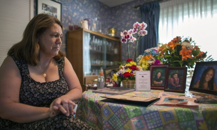 Dorothy McIntosh Shuemake, mother of Alison Shuemake, with a table of pictures and mementos of her daughter, who died of a heroin overdose in Middletown, Ohio, on Aug. 18, 2015. (AP Photo/John Minchillo)