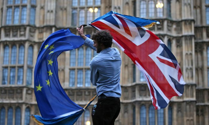 A man waves both a Union flag and a European flag outside The Houses of Parliament at an anti-Brexit protest in central London on June 28. (JUSTIN TALLIS/AFP/Getty Images)