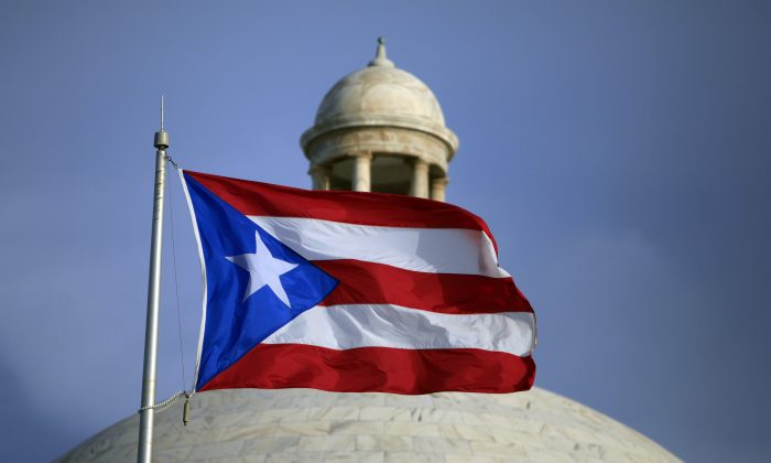 The Puerto Rican flag flies in front of Puerto Rico's Capitol as in San Juan on July 29, 2015.  (AP Photo/Ricardo Arduengo)
