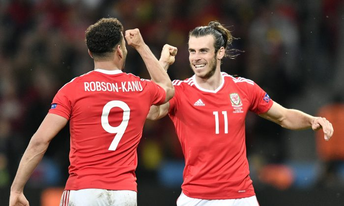 Wales' Hal Robson Kanu, left, celebrates with Gareth Bale after scoring his side's second goal during the Euro 2016 quarterfinal soccer match between Wales and Belgium, at the Pierre Mauroy stadium in Villeneuve d'Ascq, near Lille, France, Friday, July 1, 2016. (AP Photo/Martin Meissner)
