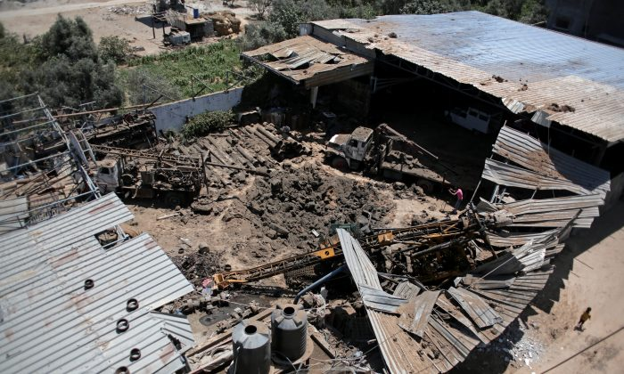 A Palestinian boy walks next to a destroyed workshop that was hit by an early morning Israeli airstrike, in Gaza City, on July 2, 2016. (AP Photo/Khalil Hamra)