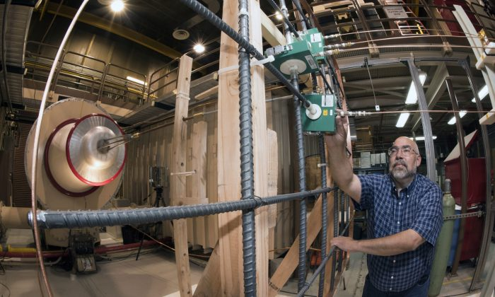 In this undated photo provided by Sandia National Laboratories, researcher Leonard Martinez makes an adjustment at the Lightning Simulator lab in Albuquerque, N.M. Researchers are using the simulator to test their knowledge of lightning protection systems by looking at how lightning currents flow through rebar lattice structures. (Randy Montoya/Sandia National Laboratories via AP)