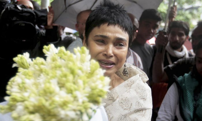 An unidentified woman reacts as she brings flowers to pay respect to the people who died at Holey Artisan Bakery in Dhaka's Gulshan area, Bangladesh, on July 3, 2016. (AP Photo)