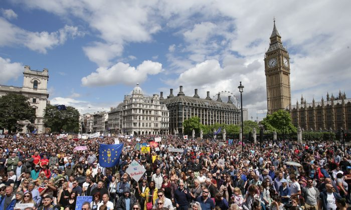 """""""Remain"""" supporters demonstrate in Parliament Square, London, to show their support for the European Union in the wake of the referendum decision for Britain to leave the EU, known as """"Brexit"""", Saturday July 2, 2016. Demonstrators wearing EU flags as capes and with homemade banners saying """"Bremain"""" and """"We Love EU"""" gathered on the streets for the March for Europe rally. At rear right is the Elizabeth Tower containing Big Ben. (Daniel Leal-Olivas/PA via AP)"""