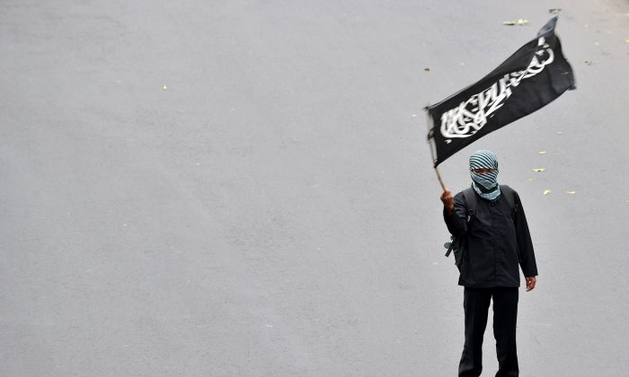 A Muslim supporter of the Indonesian section of the pan-Islamic organization Hizbut Tahrir holds a flag in the road during a protest against this week's visit by President Barack Obama at the U.S. embassy in Jakarta on Nov. 7, 2010. (Adek Berry/AFP/Getty Images)