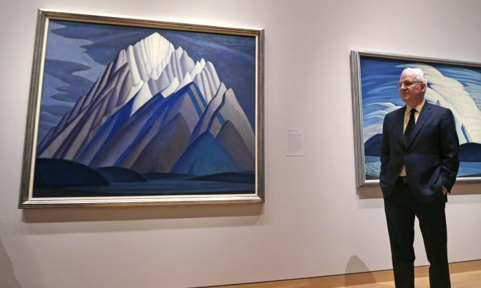"""Actor and comedian Steve Martin, who is guest curator of an exhibition at the Museum of Fine Arts devoted to Canadian modernist Lawren Harris, stands next to Harris's """"Mountain Forms"""" painting during a gallery preview at the museum in Boston, Friday, March 11, 2016. """"The Idea of North: The Paintings of Lawren Harris"""" runs through June 12. (AP Photo/Charles Krupa)"""