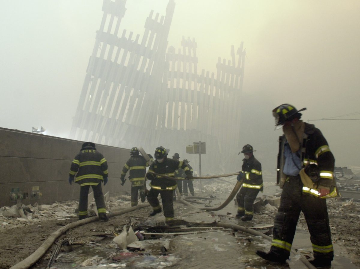 Firefighters work beneath the destroyed mullions, the vertical struts which once faced the soaring outer walls of the World Trade Center towers, after a terrorist attack on the twin towers in New York on Sept. 11, 2001. (AP Photo/Mark Lennihan)