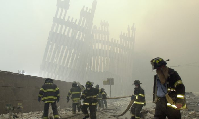 Firefighters work beneath the destroyed mullions, the vertical struts which once faced the soaring outer walls of the World Trade Center towers, after a terrorist attack on the twin towers in New York on Sept. 11, 2001. (Mark Lennihan/FILE PHOTO via AP)
