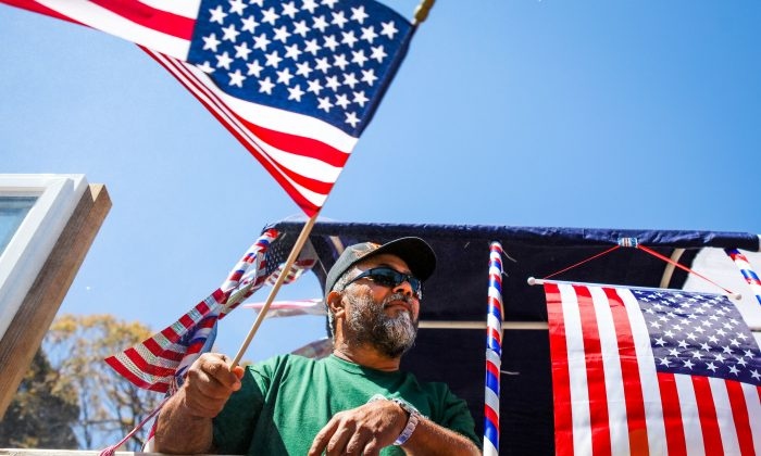 A man waves an American flag from a float during the 4th of July Parade in Alameda, Calif. (GABRIELLE LURIE/AFP/Getty Images)
