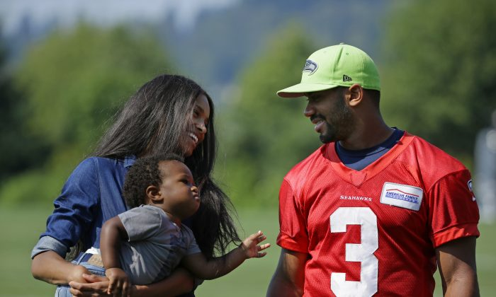 Seattle Seahawks quarterback Russell Wilson, (R) walks with his girlfriend, entertainer Ciara Harris, and Harris' son Future on Aug. 13, 2015. (AP Photo/Ted S. Warren)