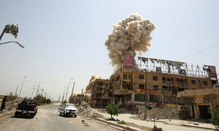TOPSHOT - Smoke rises in the city of Fallujah on June 30, 2016 as Iraqi forces destroy a booby-trapped building after they've recaptured the city from Islamic State (IS) group jihadists. Iraqi forces have retaken full control of Fallujah, a longtime jihadist bastion just 50 kilometres (30 miles) west of Baghdad, after a vast operation that was launched in May. / AFP / AHMAD AL-RUBAYE        (Photo credit should read AHMAD AL-RUBAYE/AFP/Getty Images)