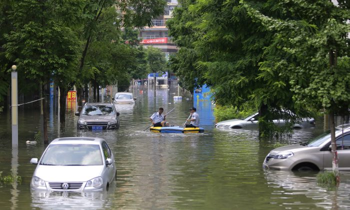 Rescuers on inflatable boats in the flooded of South Lake community of Wuhan, central China, on July 7 2016.  (Wang He/Getty Images)