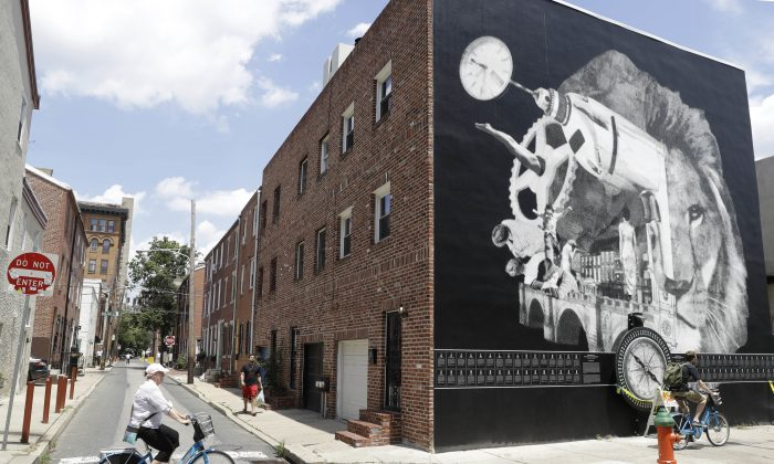 "In this Wednesday, July 6, 2016, photo, cyclists move past a Philadelphia Mural Arts Program piece by New Orleans artist Candy Chang called ""The Atlas of Tomorrow: A Device for Philosophical Reflections,"" in Philadelphia. The piece features a 6-foot dial that visitors are encouraged to twirl while thinking of their challenges. (AP Photo/Matt Rourke)"